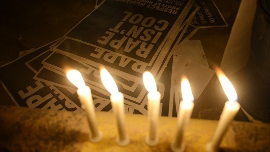 Posters are lit by candlelight during a protest in New Delhi on December 31, 2012. As he recalls the attack that killed his best friend and left him grievously wounded, the young IT operator still can't fathom the depravity they encountered after a night out at a Delhi shopping mall.