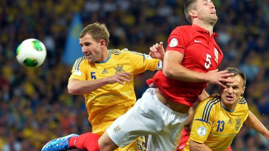 England defender Gary Cahill gets a shove from Ukraine's Olexandr Kucher (L) during their 2014 FIFA World Cup European zone Group H match in Kiev on September 10, 2013. The game ended 0-0
