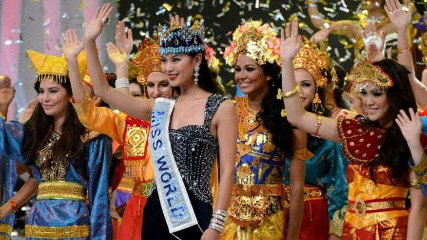 Miss World 2012, Wenxia Yu (centre) of China, waves with contestants from Miss World 2013 wearing traditional Indonesian costumes during the opening ceremony in Nusa Dua, Bali, on September 8, 2013.