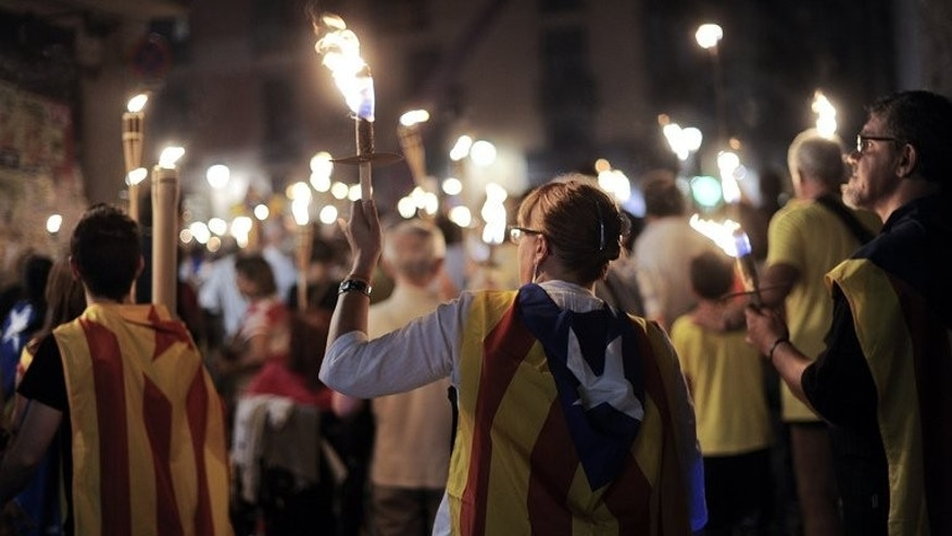 People hold torches during a rally as part of a campaign for independence from Spain, on the Fossar de les Moreres square in Barcelona on September 10, 2013. Thousands of people in Catalonia are poised to unite Wednesday to form a 400-kilometre (250-mile) human chain in a bold push for independence from Spain which is fiercely opposed by Madrid.