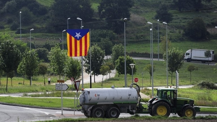 "A tractor passes a ""Senyera"", the independentist flag, near Barcelona on September 9, 2013. Thousands of people in Catalonia are poised to unite Wednesday to form a 400-kilometre (250-mile) human chain in a bold push for independence from Spain which is fiercely opposed by Madrid"