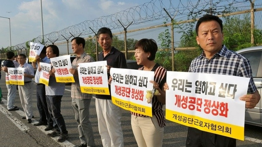 South Korean Kaesong-based workers hold placards reading 'We would like to work' on August 14, 2013. The industrial park was closed down five months ago amid soaring military tensions.