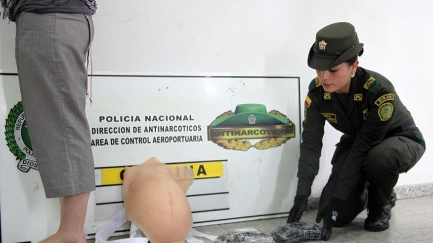 A picture released by Colombia's Police on September 11, 2013 shows Canadian national Leah Ritchie (L) after being detained at Bogota airport while pretending to be pregnant and attempting to board a flight carrying 2kg of cocaine hidden under a latex belly.