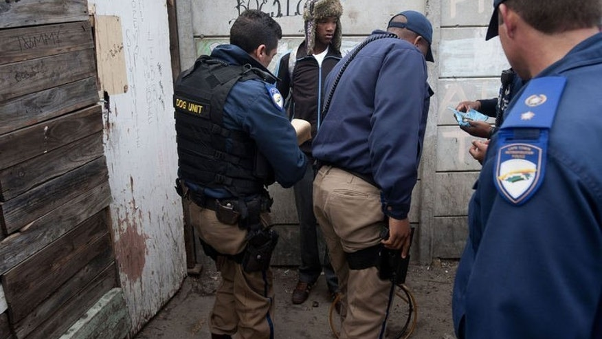 Cape Town metro police special operations officers seize marijuana, packed in a blue plastic bag (right) from two young men (C and one not on picture) in Manenburg, about 15 kms from the centre of Cape Town. Search operations take place daily, with police hunting Manenberg's 1,000 most wanted criminals, those suspected of offences ranging from murder to drug possession.