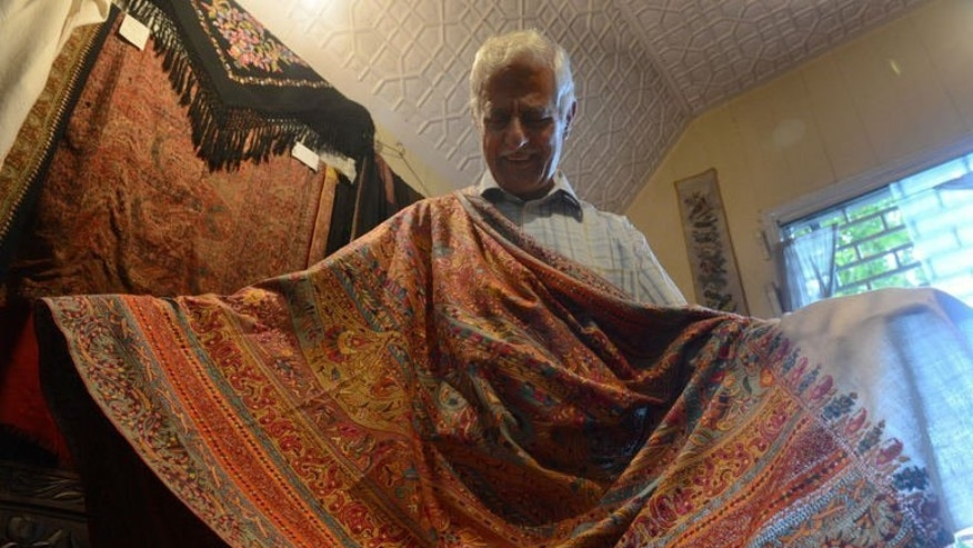 Mohammad Sadiq Wani, who sells Kashmir handicraft products, displays a hand-embroidered Pashmina shawl at his shop in Srinagar on August 21, 2013.