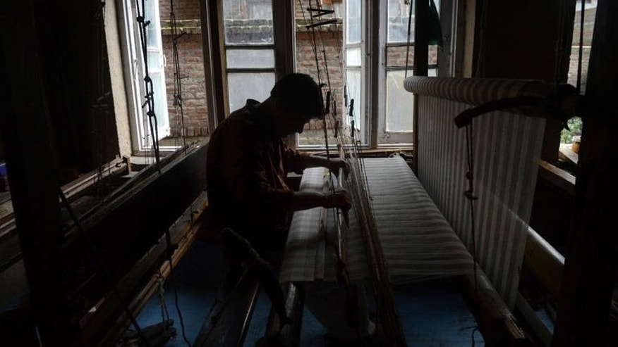 A local artisan weaves a Kashmir Pashmina shawl on a traditional handloom in Srinagar on August 20, 2013.