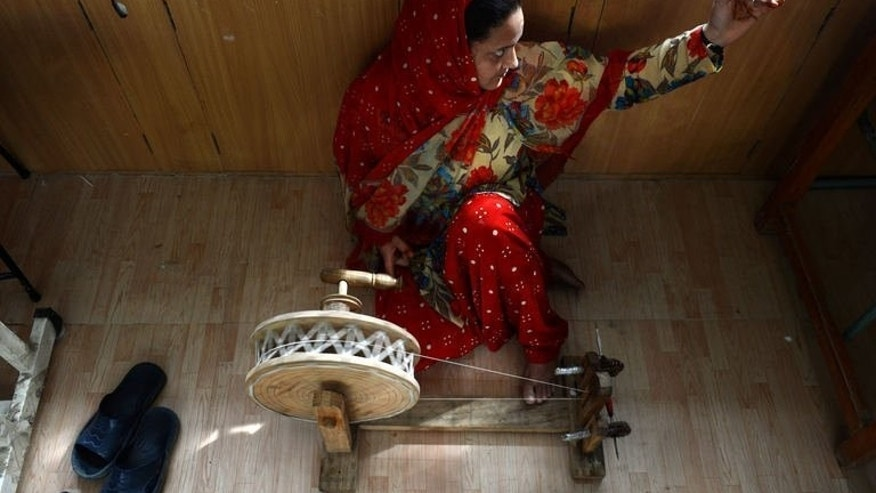 A woman spins Pashmina yarn on a traditional spinning wheel at the Sher-i-Kashmir University of Agricultural Sciences and Technology campus outside Srinagar on August 16, 2013.