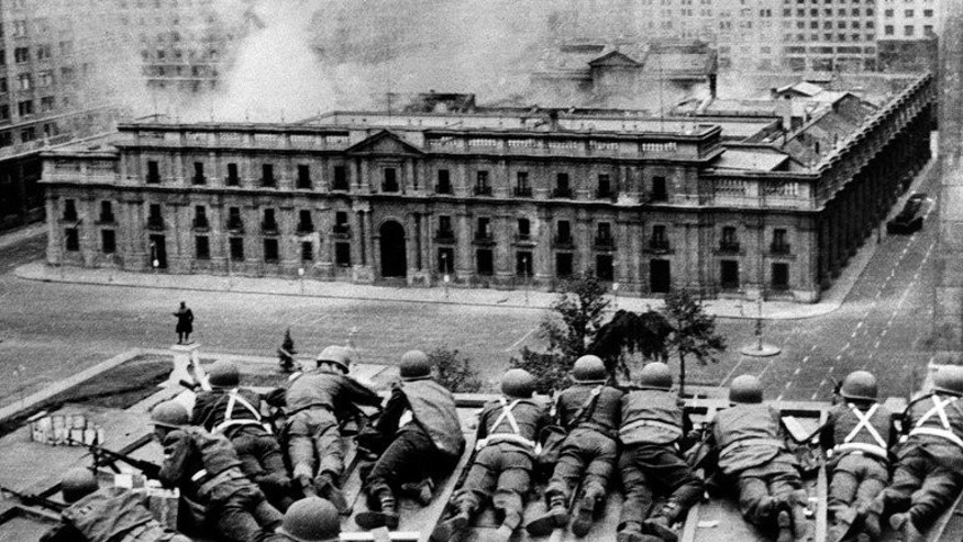 Chilean troops positioned on a rooftop fire on the La Moneda Palace in Santiago, on September 11, 1973.