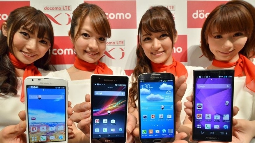 Models show off new smartphone handsets in Japan on May 15, 2013. Firms including Samsung and Apple use Hynix components in their products.