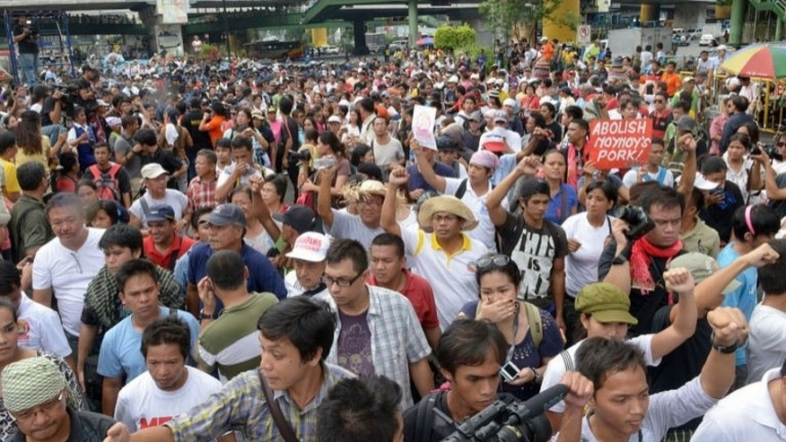 "A crowd of Filipinos gather to oppose ""pork barrel"" allocations given to legislators, which protesters condemned as a major source of graft, at a public square in Manila on September 11, 2013."