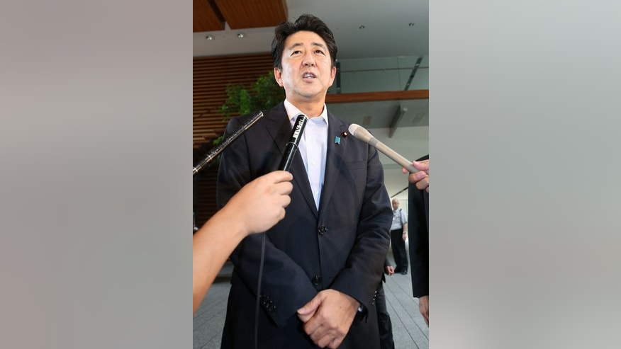 Japanese Prime Minister Shinzo Abe speaks to reporters at his official residence in Tokyo on September 10, 2013. China's Xinhua has accused Abe of turning a blind eye to the nation's 'beautifying of atrocious wartime crime'.