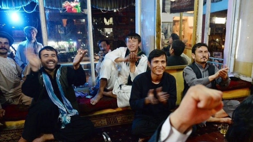 Afghans react as they watch on television the South Asian Football Federation Championship match between India and Afghanistan, in Kabul on September 11, 2013.