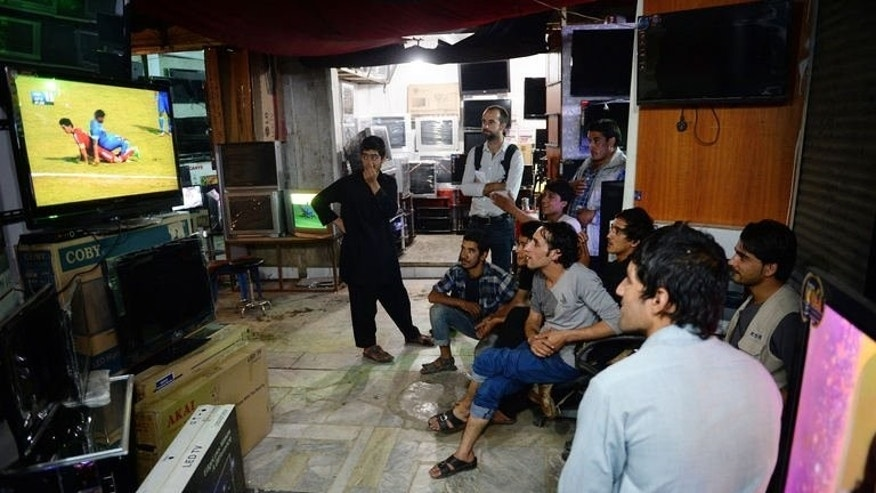 Afghans watch a large TV screen featuring the South Asian Football Federation Championship match between India and Afghanistan, in Kabul on September 11, 2013.