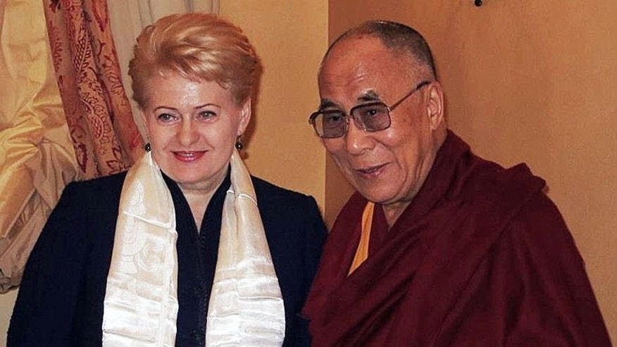 This handout released by the Press service of the President of Lithuania shows Lithuanian President Dalia Grybauskaite (L) shaking hands during a private meeting with exiled Tibetan spiritual leader the Dalai Lama in Vilnius on September 11, 2013.