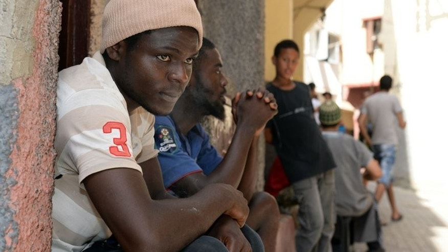 Senegalese immigrants sit in front of a building in Rabat on August 23, 2013. Morocco announced a new immigration policy, pledging to review cases according to specific criteria, following sharp criticism over its treatment of sub-Saharan migrants.