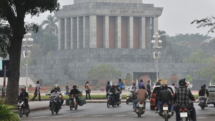 Motorcyclists ride past the mausoleum of late president Ho Chi Minh on February 24, 2010 in Hanoi.
