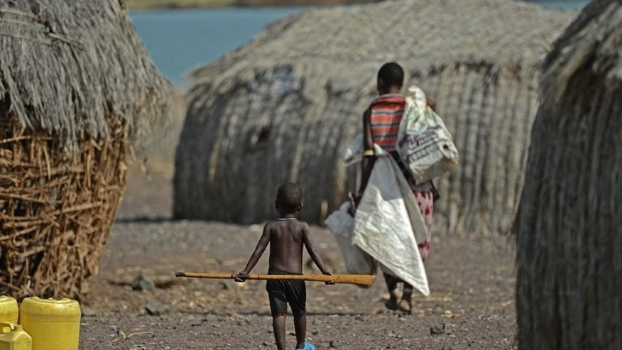 A mother and child walk in the village of Komote on the shores of Lake Turkana, northern Kenya on May 18, 2012. The Kenyan government and UNESCO announced the discovery of a potentially vast supply of underground water in the impoverished, drought-stricken extreme north of the country.