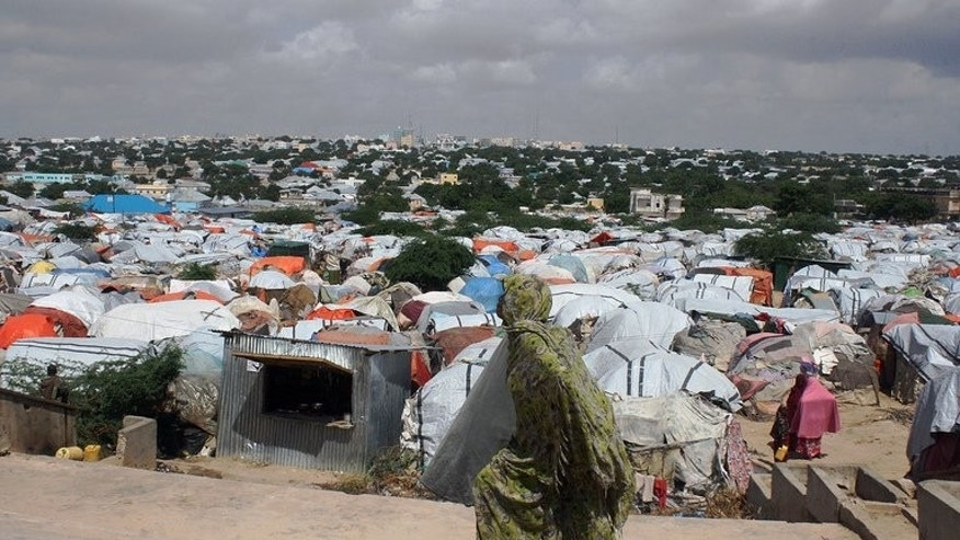 A Somali refugee walks in front of a camp for internally displaced people in Mogadishu on December 4, 2012. War-torn Somalia will be dealt a devastating blow if international banks carry out threats to stop money transfer systems sending funds that dwarf levels of foreign aid, experts warned.