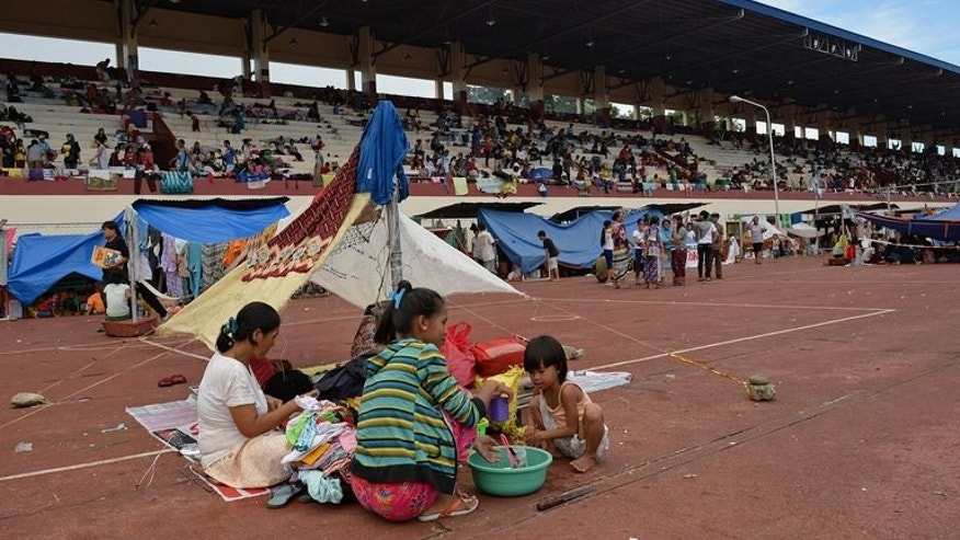 Many people living near to the fighting in Zamboanga fled to a nearby sports stadium to seek shelter as fighting raged, on September 10, 2013. Government officials were struggling to provide facilities for thousands of people.