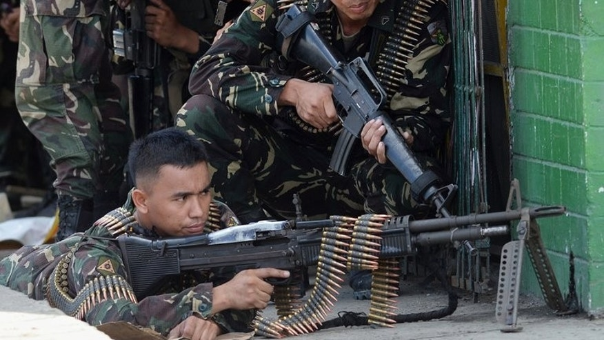 Philippine troops take cover from enemy snipers in Zamboanga on September 11, 2013. Twelve people have been killed so far in the stand-off, military officials say.