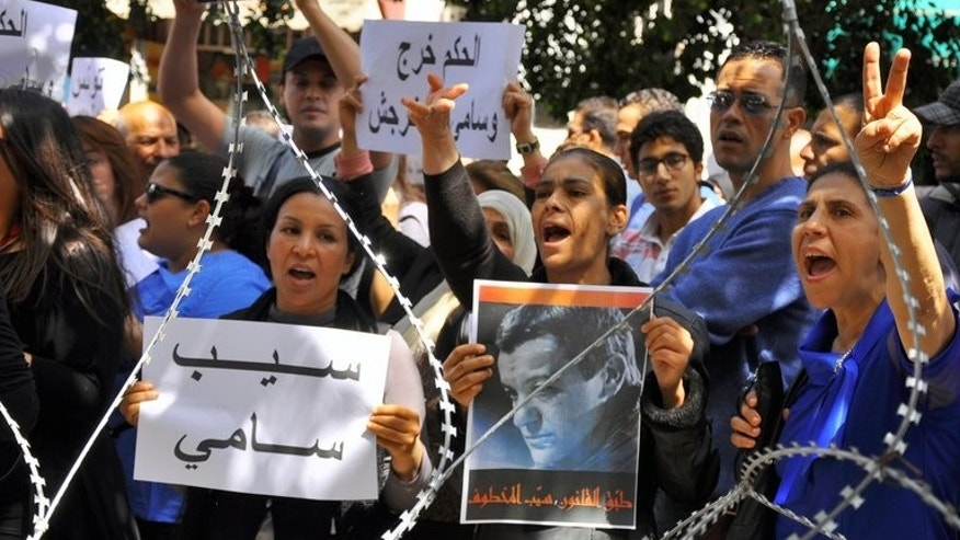 Demonstrators hold pictures of Sami El-Fehri, jailed boss of the Ettounsiya TV channel, as they shout slogans calling for his release outside the court in Tunis on April 15, 2013.