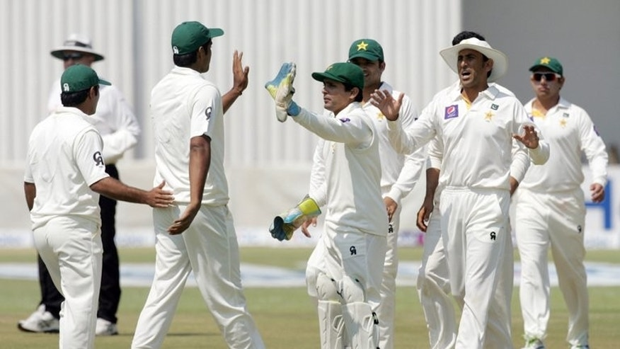 Pakistan players celebrate a Zimbabwe wicket at the Harare Sports Club on Wednesday. Pakistan endured a frustrating morning as it took them more than an hour and one ball short of 20 overs to capture the last two Zimbabwe wickets after the home side resumed at 235 for eight.