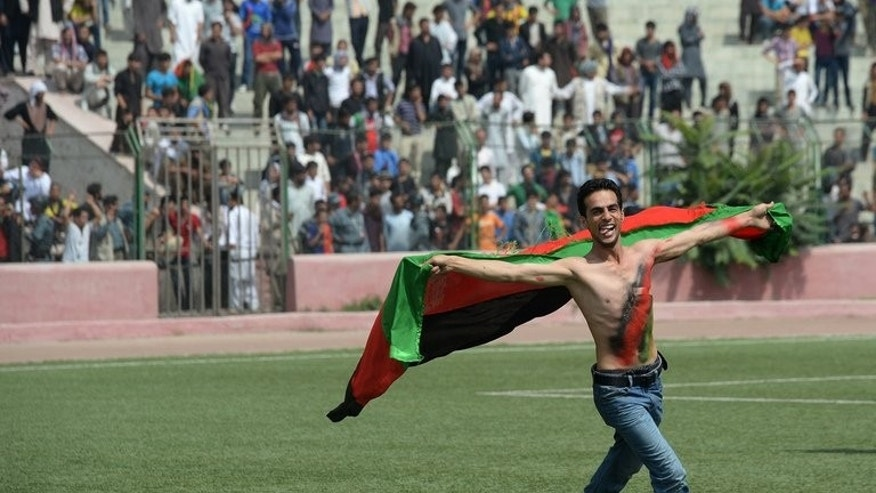 An Afghan football fan runs with the national flag as he celebrates the national football team's victory, in Kabul on September 12, 2013. The team stunned six-time champions India 2-0 Wednesday night to win the South Asian Football Federation (SAFF) title in the Nepalese capital Kathmandu.
