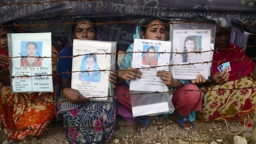 Mourners in Savar on August 2, 2013, hold up portraits of their missing relatives, presumed dead following the Rana Plaza garment building collapse. A two-day meeting of high street clothing brands and pressure groups aimed at reaching a compensation deal for victims of two Bangladesh factory disasters has ended in failure, organisers said.