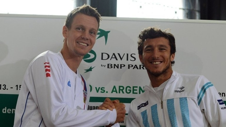 "Czech Republic's Tomas Berdych (L) shakes hands with Argentina's Juan Monaco in Prague on September 12, 2013. ""We have our home crowd, which helps us a lot and we have the strongest team possible. For us, the goal is to make three points,"" Berdych said."