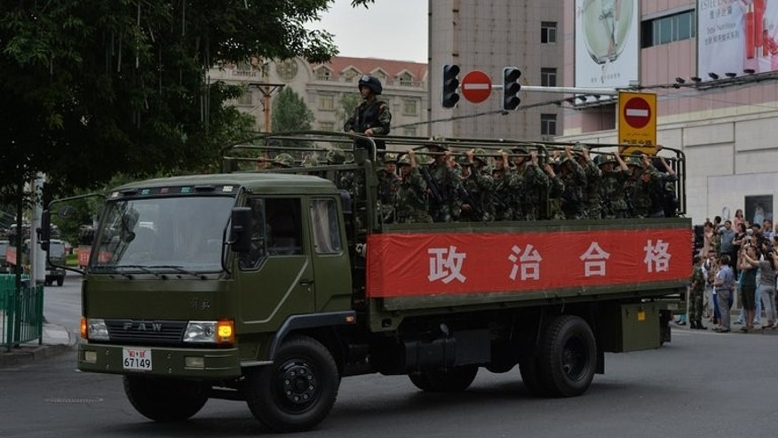 Chinese paramilitary police armed with assault rifles ride in trucks during a show of force ceremony in Urumqi after a series of terrorist attacks recently hit Xinjiang Province, on June 29, 2013.