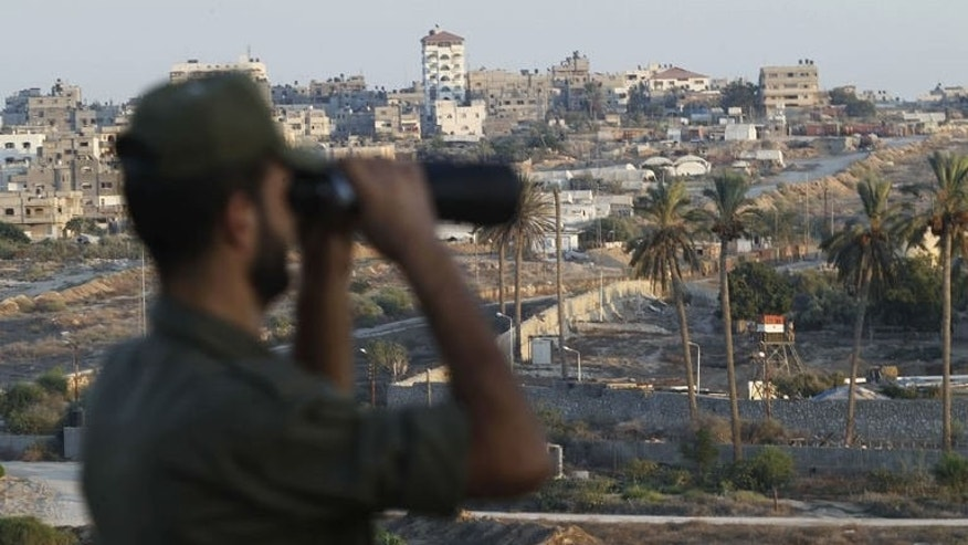 A Palestinian Hamas security guard looks through a pair of binoculars while on duty at the border between Egypt and Gaza Strip, in Rafah town southern Gaza Strip, on September 11, 2013.