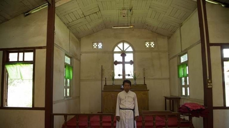 "Image taken on July 24, 2013 shows Myanmar Reverend Daniel Say Htan standing in the local Anglican church in Katha. The Anglican church, the setting for the climax of the book ""Burmese Days"", still stands and is still in use."