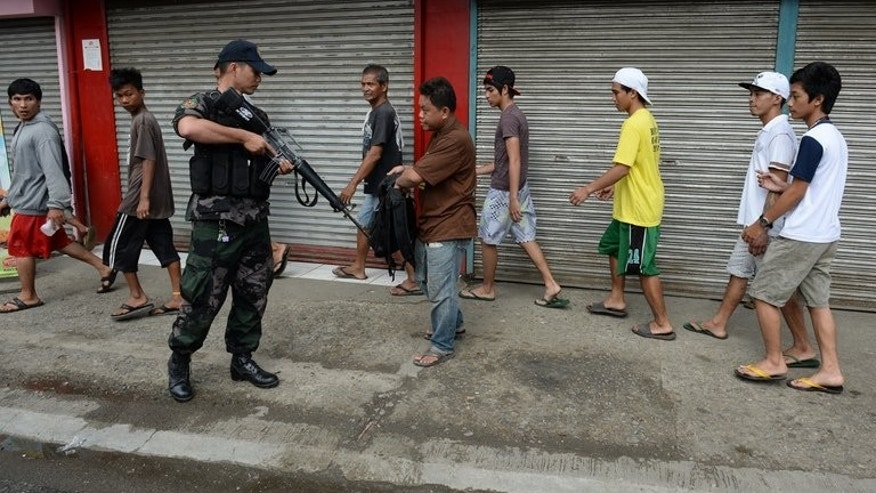 A policeman checks the bag of a pedestrian after suspected rebels clashed with police in Zamboanga on September 11, 2013. Hundreds of elite soldiers backed by police forces have surrounded about 180 guerrillas, the army says.