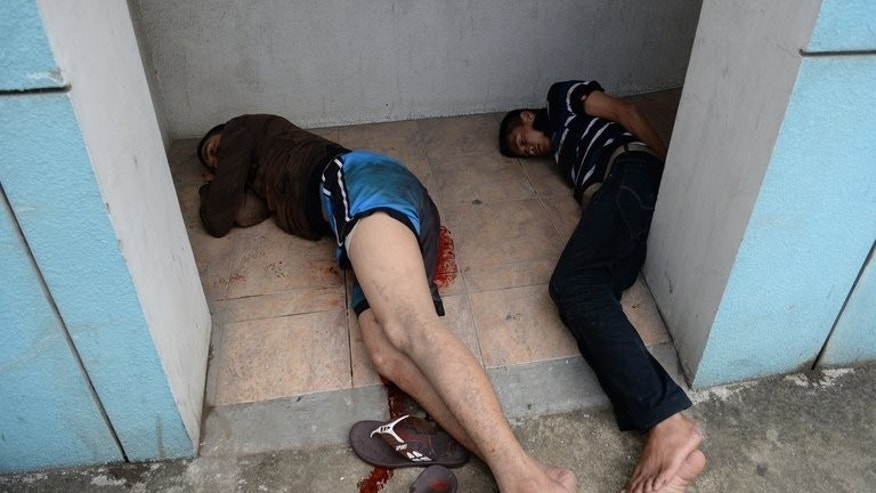 Two suspected Muslim rebels lie on a pavement after clashing with policemen in Zamboanga City on September 11, 2013. Gunmen from the Moro National Liberation Front (MNLF), which has waged a decades-long campaign for independence, have used villagers as human shields in their assault on the city.