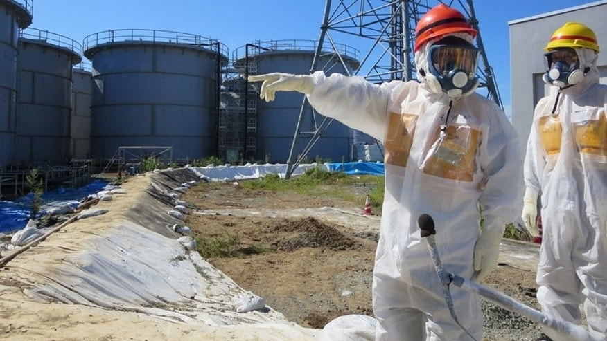 Japan's industry minister Toshimitsu Motegi (red helmet) inspects contamination water tanks on August 26, 2013. Tokyo has voiced anger over cartoons published in a French newspaper mocking the decision to host the 2020 Olympic Games in Japan.