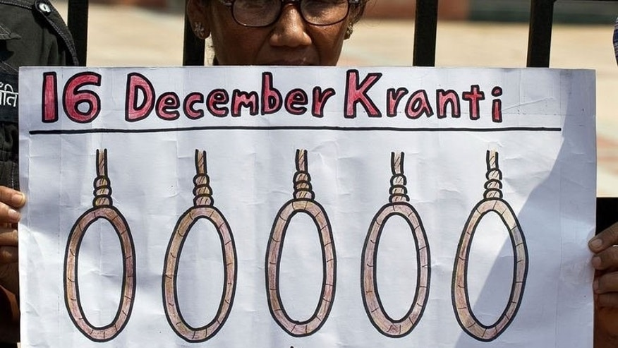 An Indian woman holds a placard demanding the death sentence during a protest outside the Saket Court complex in New Delhi on September 11, 2013.
