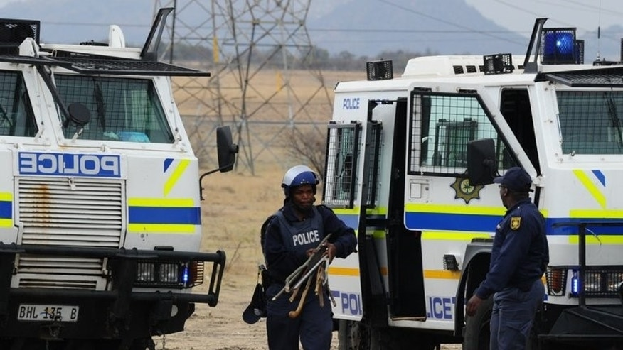 South African police carry weapons taken from stricking miners in Marikana on September 15, 2012. Hundreds of demonstrators marched on South African government buildings to protest at a lack of state funding for survivors of shootings at the Marikana mine, where 44 people died.
