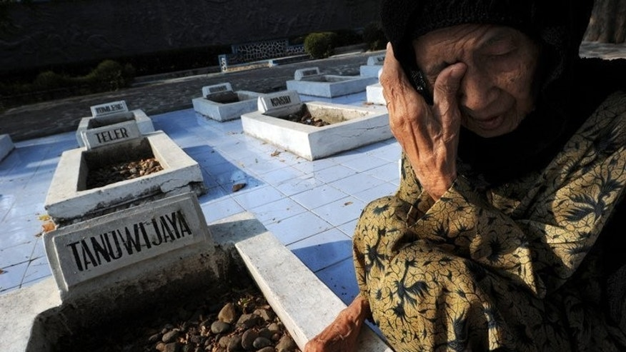 "An Indonesian widow visits the tomb of her husband at the Rawagede monument of independence -- where victims of a 1947 massacre by Dutch military troops are buried in West Java province -- on September 15, 2011. The Netherlands has sought to ""close a difficult chapter"" with its former colony Indonesia by publicly apologising for summary executions carried out by the Dutch army in the 1940s."