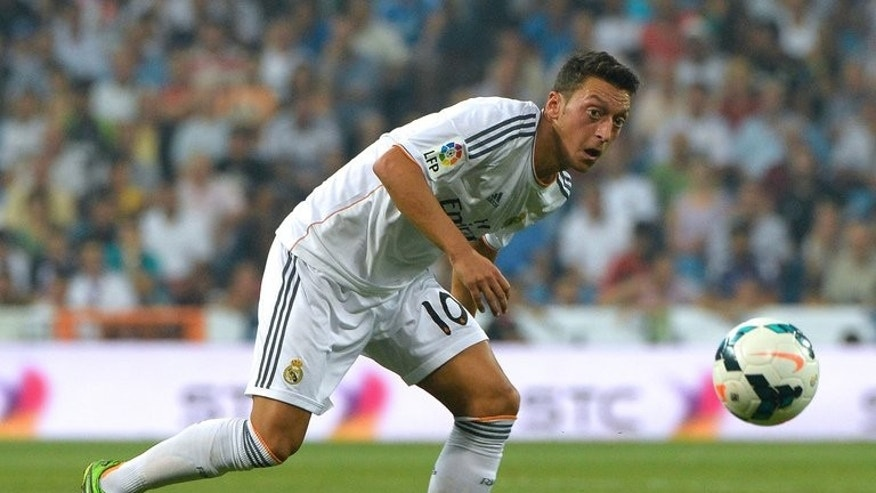 Then-Real Madrid midfielder Mesut Ozil eyes the ball during their Spanish league match against Real Betis in Madrid on August 18, 2013. Record Arsenal signing Mesut Ozil said on Thursday that he believes the club can challenge for the English Premier League title this season.