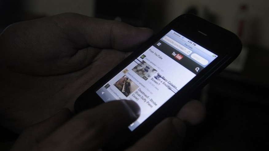 A Pakistani cell phone user browses YouTube on his mobile phone in Quetta on December 29, 2012. In a dingy Internet cafe, Abdullah gets round the censors with one click and logs onto YouTube, officially banned for a year and at the heart of Pakistan's cyberwar for control of the web.
