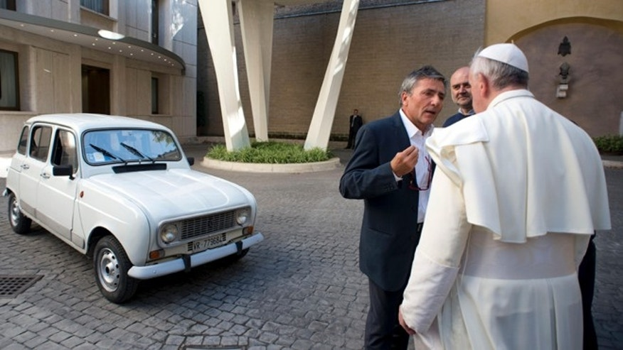 In this Saturday, Sept. 7, 2013 picture made available by the Vatican newspaper l'Osservatore Romano, Pope Francis looks at a Renault 4L donated to him by Rev. Renzo Zocca, not pictured, as he speaks with Zocca's assistant Luigi Macchioni, left, at the Vatican. (AP Photo/L'Osservatore Romano)