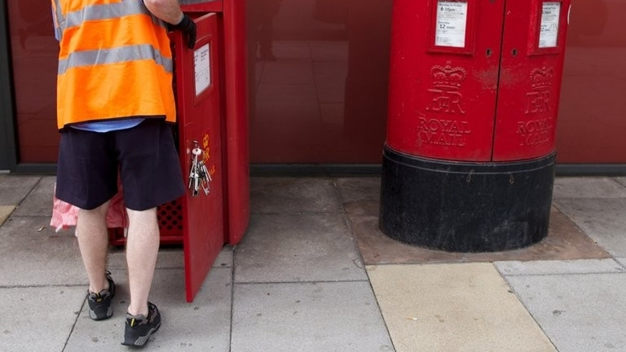 A postman empties a Royal Mail post box in London on July 10, 2013. Britain's government on Thursday officially launched plans to privatise more than half of Royal Mail, saying an initial sale of shares in the state-run postal service would occur within weeks.