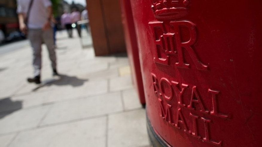 A Royal Mail post box stands on a street in London on July 10, 2013. Around 150,000 staff will be eligible to get a free stake in the business under Britain's largest employee share scheme of any major British privatisation for almost 30 years.