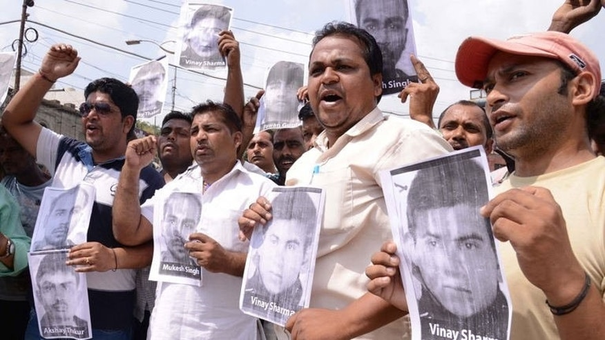 Indian activists of the Bhartiya Janta Party Scheduled Caste Morcha, shout slogans as they hold posters of four accused in a gang rape case of a student in New Delhi during a demonstration in Amritsar on September 11, 2013.