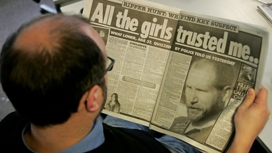 A man reads the Sunday Mirror in 2006. The publisher of Britain's Sunday Mirror newspaper said Thursday that it is being investigated for alleged phone-hacking by former staff.