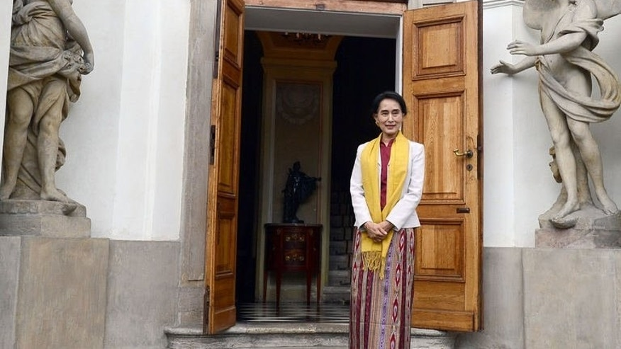 Myanmar's opposition leader Aung San Suu Kyi stands in front of Myslewicki palace after a meeting with former Polish President Lech Walesa on September 12, 2013 in Warsaw, Poland.