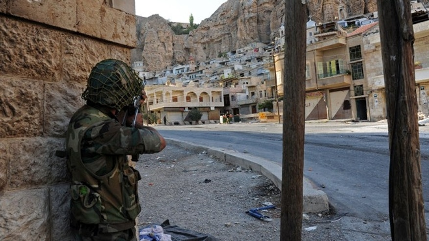 Sept. 11, 2013: In this photo released by the Syrian official news agency SANA, a Syrian government solider aims his weapon during clashes with Free Syrian Army fighters, not pictured, in Maaloula village, northeast of the capital Damascus, Syria.