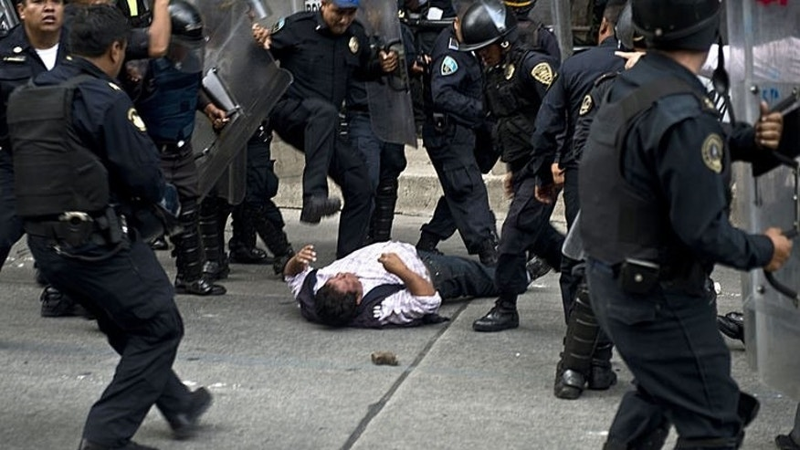 Riot police beat a teacher during a protest against the educational reforms introduced by President Enrique Pena Nieto, in Mexico City on September 11, 2013.