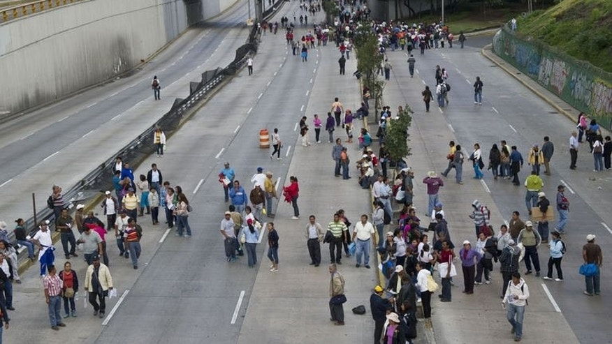 Teachers block a freeway during a protest against new educational reforms in Mexico City on September 11, 2013. Anti-riot police fortified the area around the Los Pinos residence with metal barriers and trucks to keep protesters at bay, with police saying some 12,000 teachers caused huge traffic jams as they marched across the megalopolis.