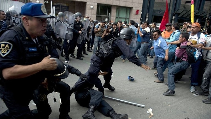 Riot police clash with teachers protesting against new educational reforms in Mexico City on September 11, 2013. T